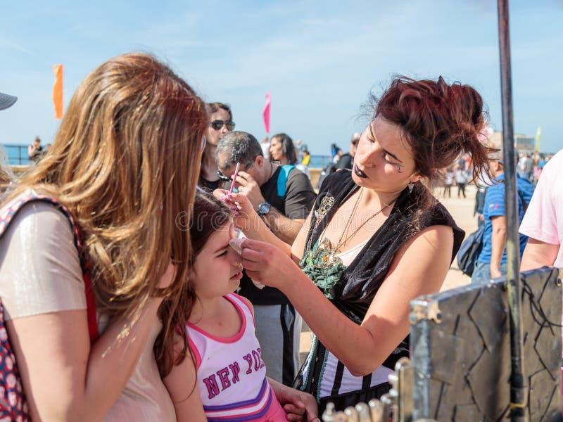 El participante del festival de Purim vestido en traje fabuloso, pone un dibujo en la cara del ` s de la muchacha en Caesarea, Is foto de archivo