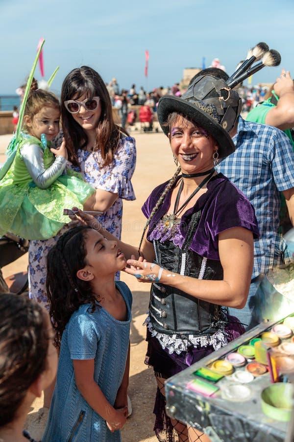 El participante del festival de Purim vestido en traje fabuloso, pone un dibujo en la cara del ` s de la muchacha en Caesarea, Is foto de archivo libre de regalías