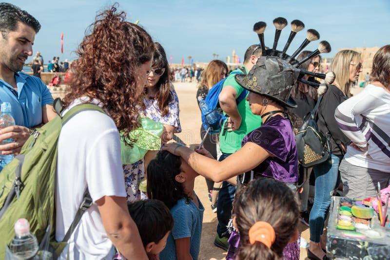 El participante del festival de Purim vestido en traje fabuloso, pone un dibujo en la cara del ` s de la muchacha en Caesarea, Is imagen de archivo libre de regalías
