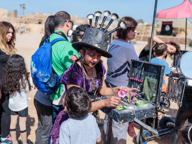 El participante del festival de Purim vestido en traje fabuloso, pone un dibujo en la cara del ` s del muchacho en Caesarea, Isra fotografía de archivo libre de regalías