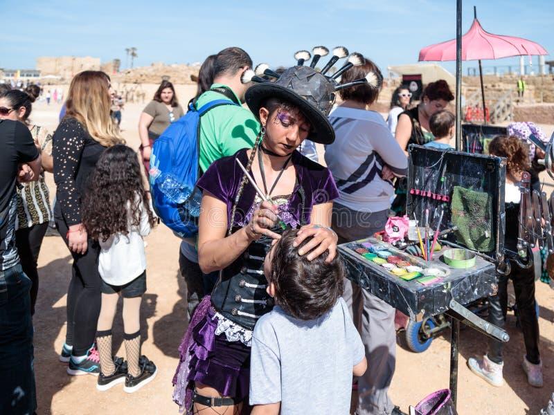 El participante del festival de Purim vestido en traje fabuloso, pone un dibujo en la cara del ` s del muchacho en Caesarea, Isra foto de archivo libre de regalías