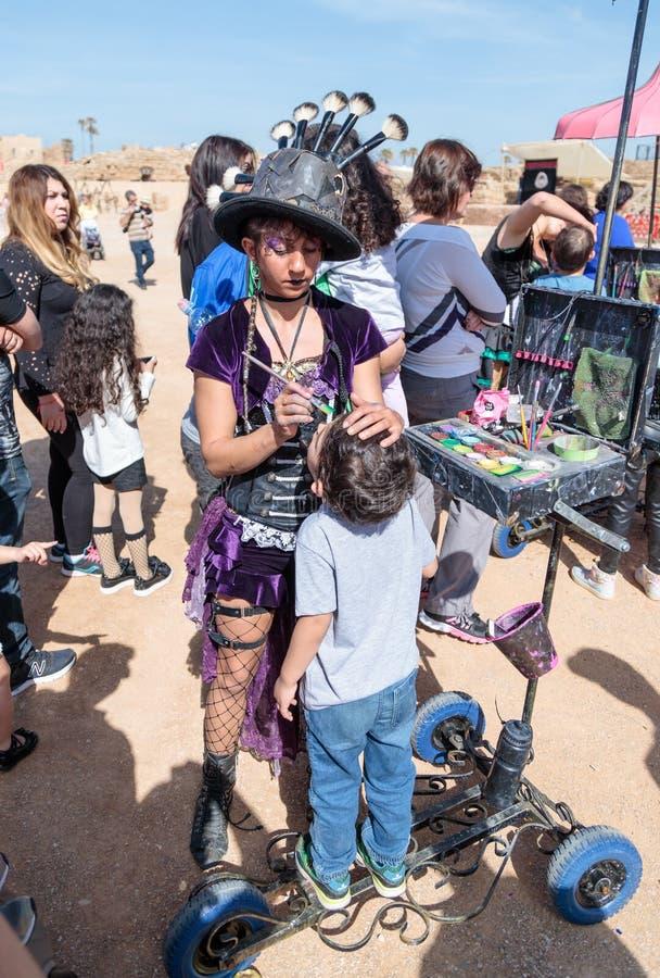 El participante del festival de Purim vestido en traje fabuloso, pone un dibujo en la cara del ` s del muchacho en Caesarea, Isra fotos de archivo