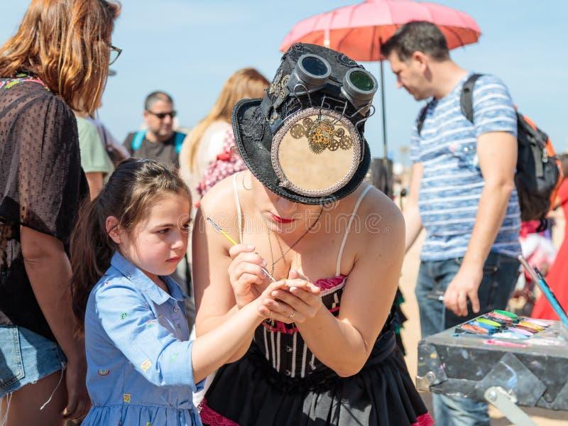 El participante del festival de Purim vestido en traje fabuloso, pone un dibujo en la mano del ` s de la muchacha en Caesarea, Is imagen de archivo