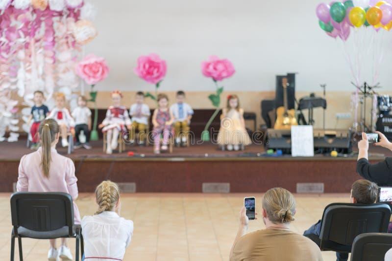 El partido de los niños en escuela primaria Los niños jovenes en etapa en guardería aparecen en padres delanteros blurry fotografía de archivo