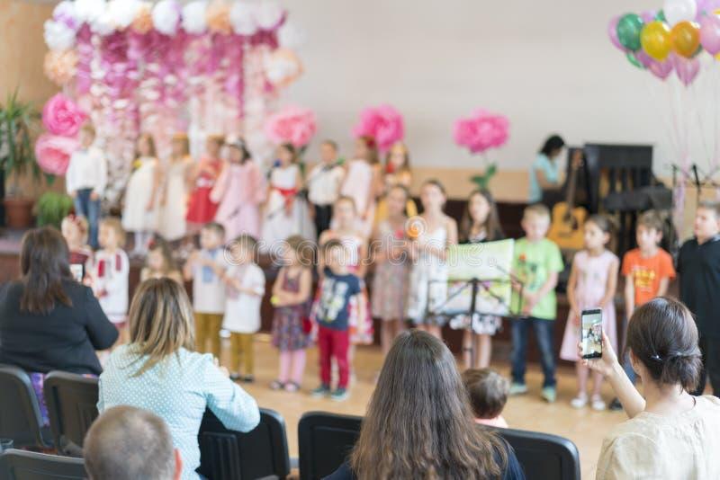 El partido de los niños en escuela primaria Los niños jovenes en etapa en guardería aparecen en padres delanteros blurry imagen de archivo libre de regalías