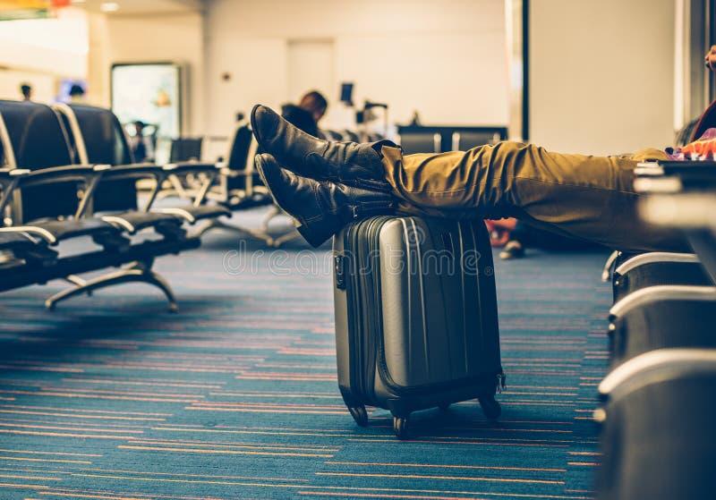 El pasajero con continúa el equipaje que espera el vuelo del retraso en el terminal de aeropuerto foto de archivo libre de regalías