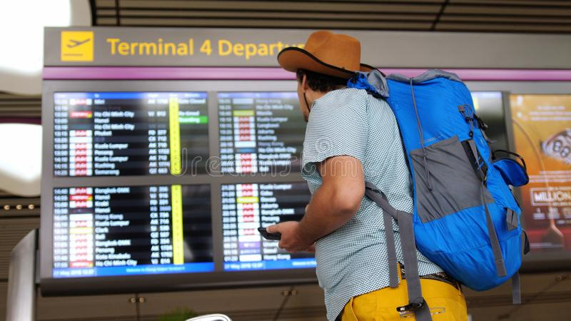 El pasajero turístico del aeropuerto internacional en teléfono móvil de las aplicaciones del sombrero se coloca con la mochila y  fotografía de archivo libre de regalías