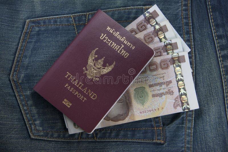 El pasaporte de Tailandia y el dinero tailandés en vaqueros embolsan imagen de archivo libre de regalías