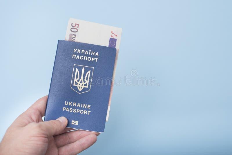 El pasaporte y euro ucranianos aprovechan la mano del ` s del hombre conce del viaje imagenes de archivo