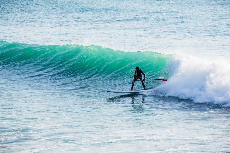 El paseo de la persona que practica surf encendido se levanta el tablero de paleta en olas oceánicas Levántese el embarque de la  imagenes de archivo