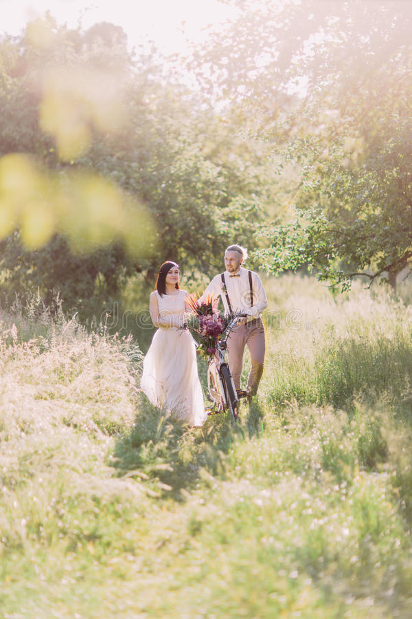 El paseo de los recienes casados con la bicicleta llena de las flores en la madera soleada imágenes de archivo libres de regalías