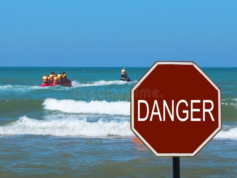 El paseo del barco de plátano con los turistas y la muestra del peligro en la playa foto de archivo libre de regalías