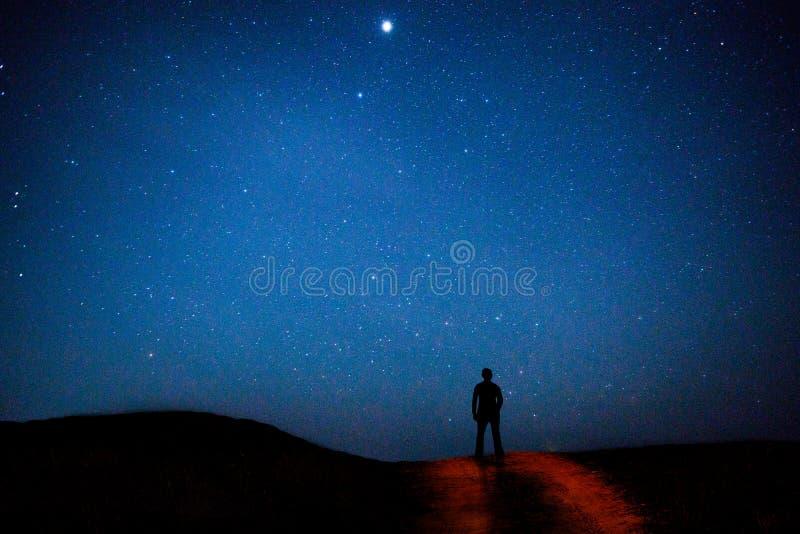 El paseo del hombre en el cielo nocturno protagoniza el fondo fotos de archivo