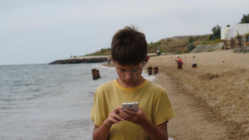 El paseo del muchacho del viajero en la playa y usar el teléfono elegante por la tarde, charlas, escribe SMS Usando un dispositiv imágenes de archivo libres de regalías