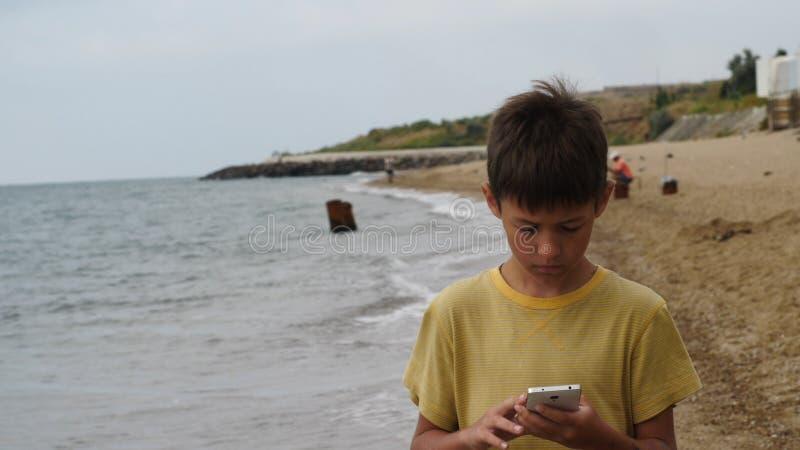 El paseo del muchacho del viajero en la playa y usar el teléfono elegante por la tarde, charlas, escribe SMS Usando un dispositiv foto de archivo