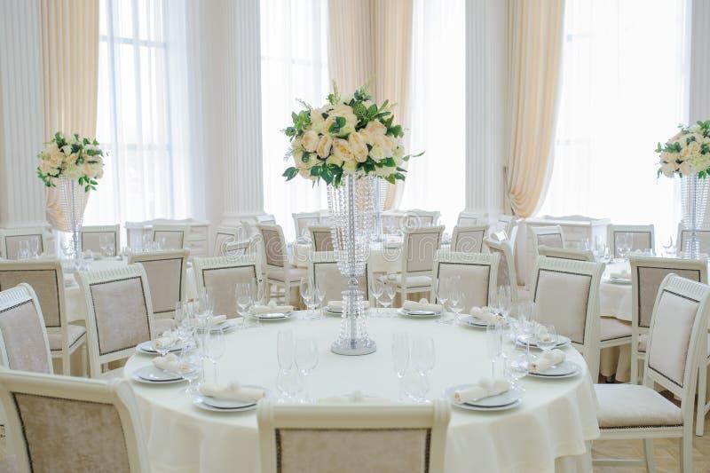 El pasillo del banquete con las mesas redondas, con los cubiertos imagen de archivo libre de regalías