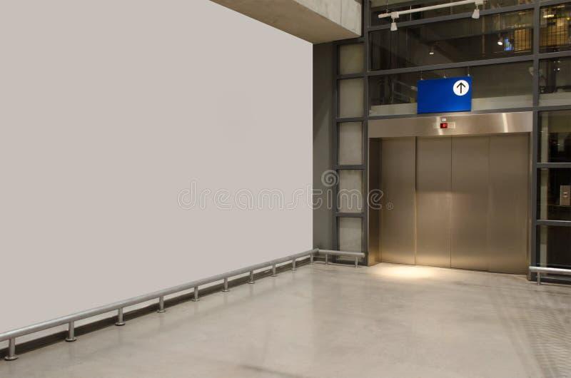 El pasillo interior en el vestíbulo con paredes blancas y ascensor en un edificio moderno y elegante de oficinas fotos de archivo libres de regalías