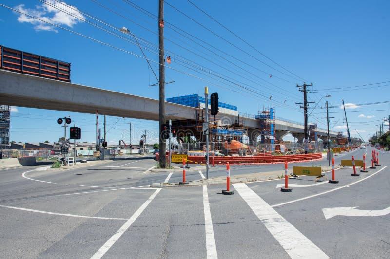 El paso a nivel del camino del centro que era substituido por el skyrail elevó vías del tren en Clayton South, Melbourne fotografía de archivo libre de regalías
