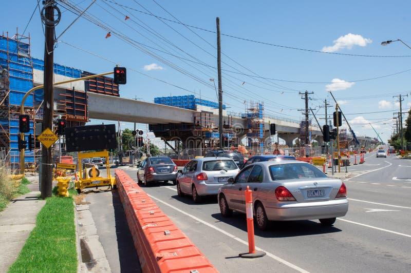 El paso a nivel del camino del centro que era substituido por el skyrail elevó vías del tren en Clayton South, Melbourne foto de archivo libre de regalías