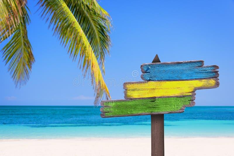 El pastel coloreó el fondo de las señales de dirección, de la playa y de la palmera foto de archivo