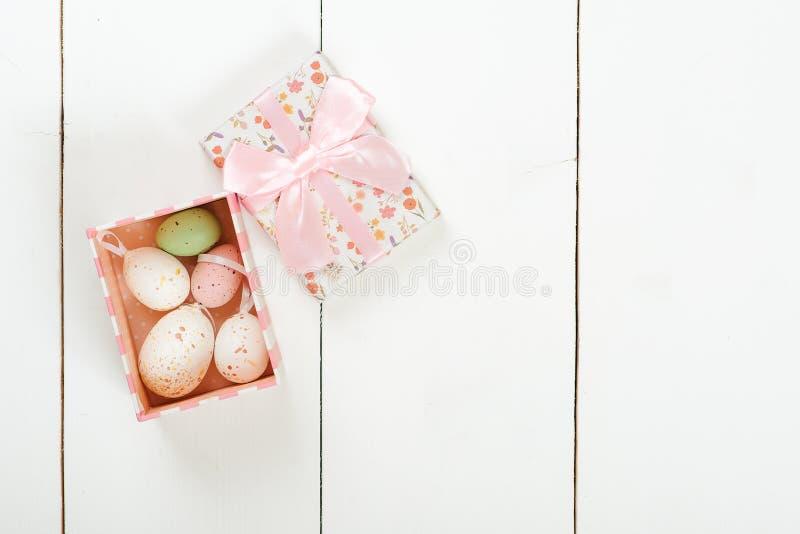 El pastel coloreó los huevos de Pascua en una caja de regalo sobre el fondo de madera blanco fotos de archivo