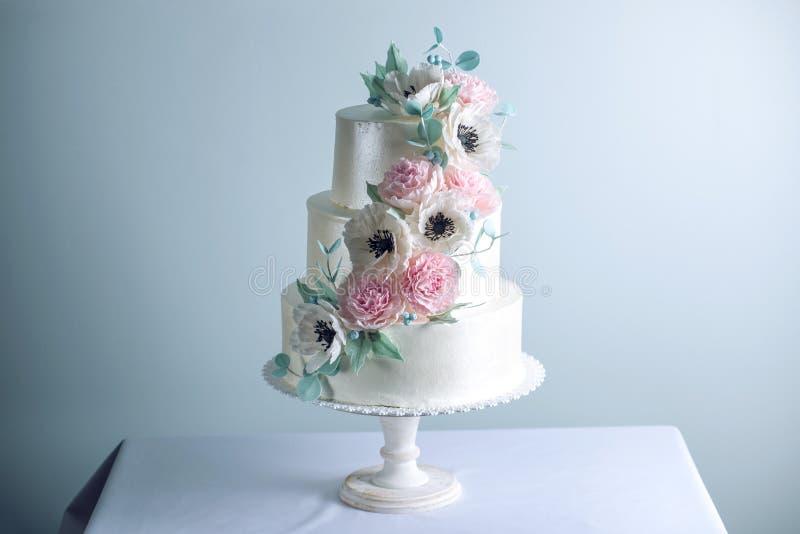 El pastel de bodas blanco con gradas tres hermosos adornado con las flores azucara peonías rosadas Concepto de postres elegantes  foto de archivo libre de regalías