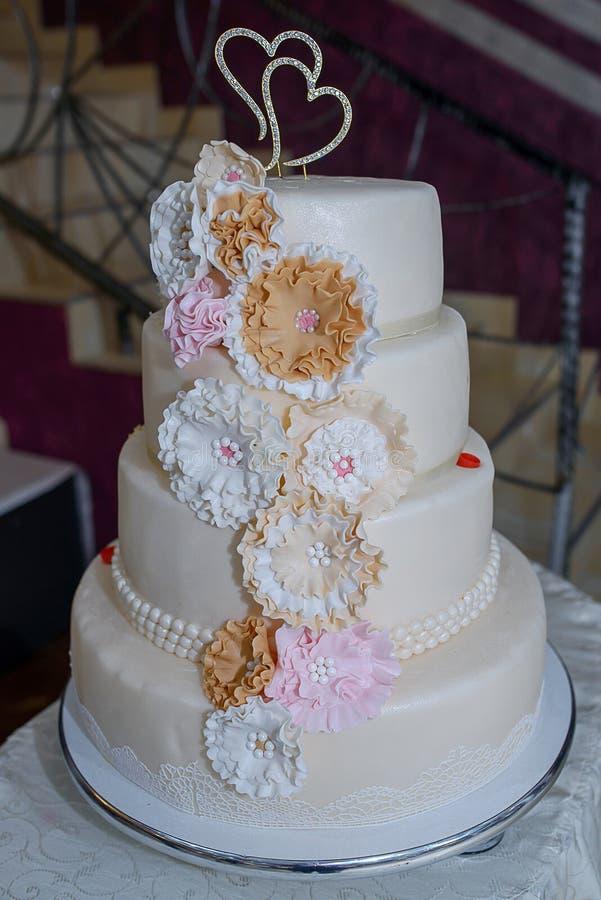 El pastel de bodas con gradas cuatro con el pastel coloreó las flores, cordón comestible y gotea los detalles, y el primero en fo imagen de archivo