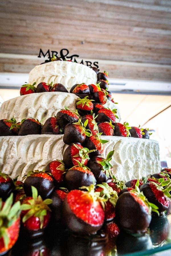 El pastel de bodas con las fresas y el chocolate imagenes de archivo