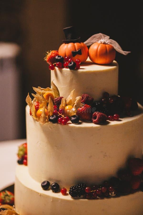 El pastel de bodas en el estilo de Halloween adornó con las bayas, las calabazas y los fizalis fotografía de archivo libre de regalías