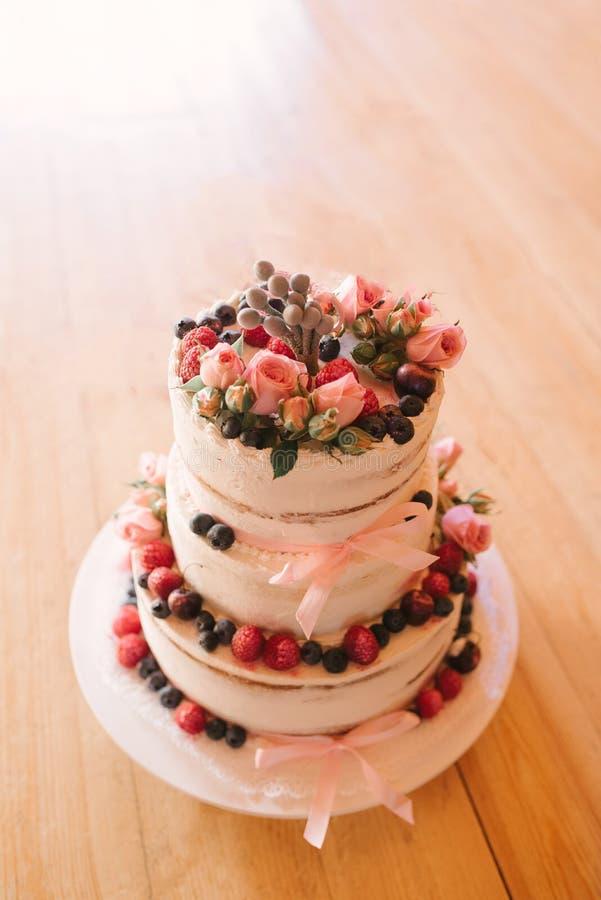 El pastel de bodas poner crema blanco hermoso adornó con las bayas frescas fotografía de archivo libre de regalías