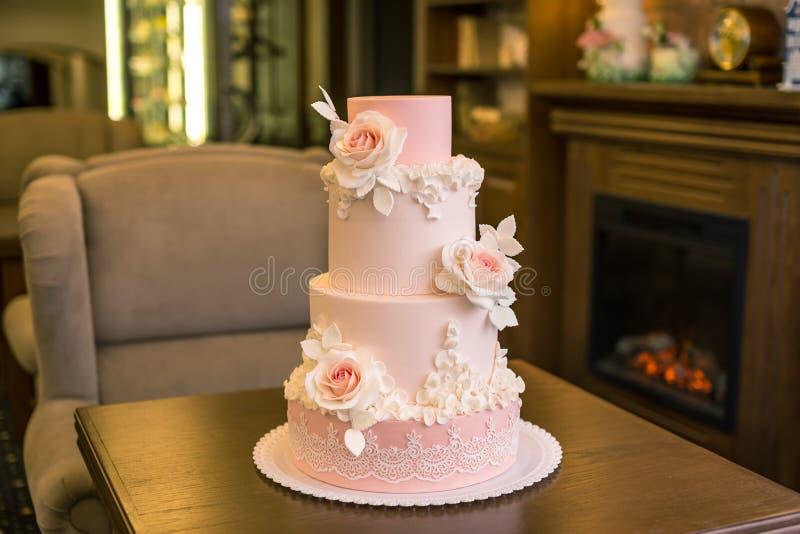El pastel de bodas rosado con gradas cuatro elegantes hermosos adornado con las rosas florece Concepto floral de la masilla del a fotografía de archivo