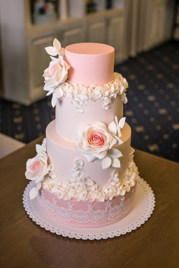 El pastel de bodas rosado con gradas cuatro elegantes hermosos adornado con las rosas florece Concepto floral de la masilla del a imagen de archivo libre de regalías