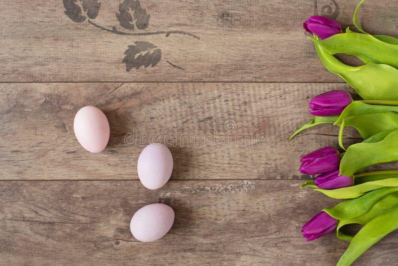 El pastel de los huevos de Pascua coloreó Flores hermosas de la primavera - tulipanes púrpuras en un fondo de madera Marco floral foto de archivo