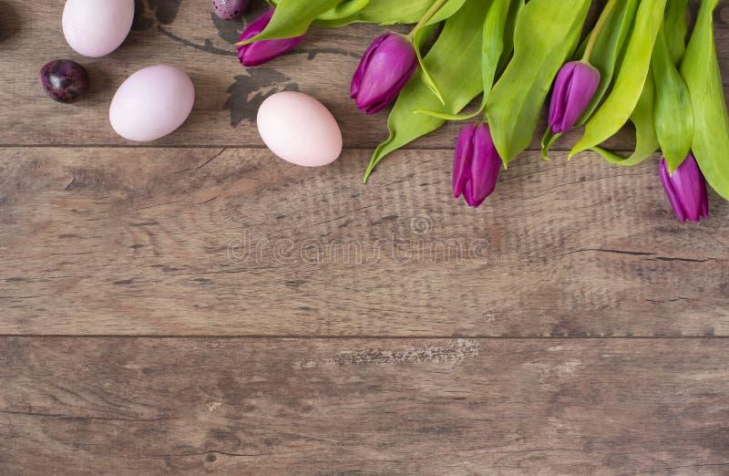 El pastel de los huevos de Pascua coloreó Flores hermosas de la primavera - tulipanes púrpuras en un fondo de madera Marco floral foto de archivo libre de regalías