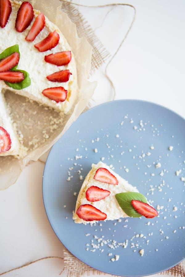 El pastel de queso brillante adornó con las fresas frescas y las hojas de la albahaca, cortaron una pieza en una placa fotos de archivo libres de regalías