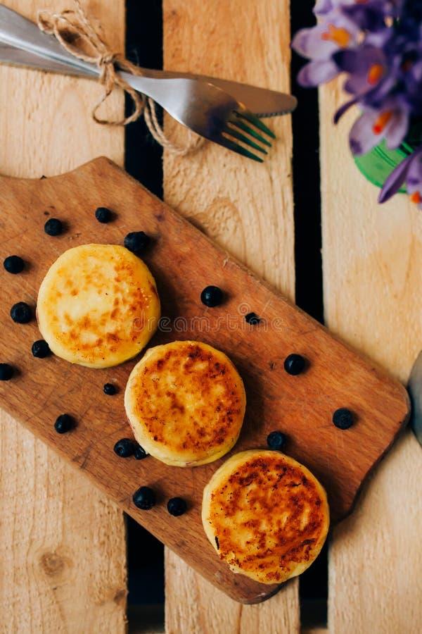 El pastel de queso con la baya una tabla de cocina de madera rodeó el cuchillo y la bifurcación tempranos de las flores de la pri foto de archivo