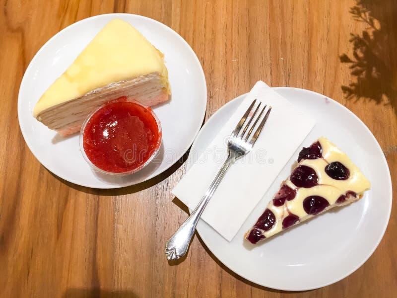 El pastel de queso del arándano y la torta del crespón con la salsa de la fresa están en el plato blanco Todos fueron colocados e imagenes de archivo