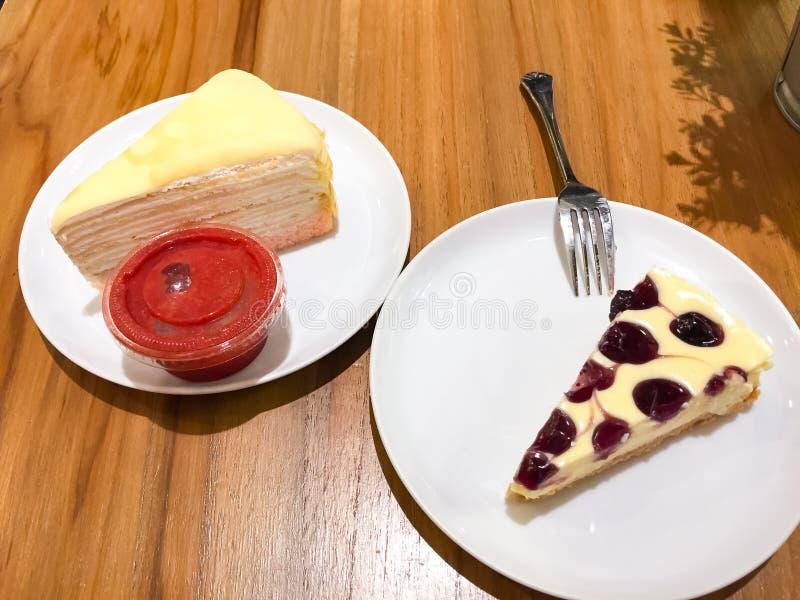 El pastel de queso del arándano y la torta del crespón con la salsa de la fresa están en el plato blanco Todos fueron colocados e fotos de archivo libres de regalías