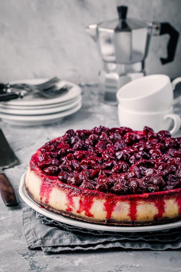 El pastel de queso hecho en casa con la base del chocolate y la cereza sauce imagen de archivo