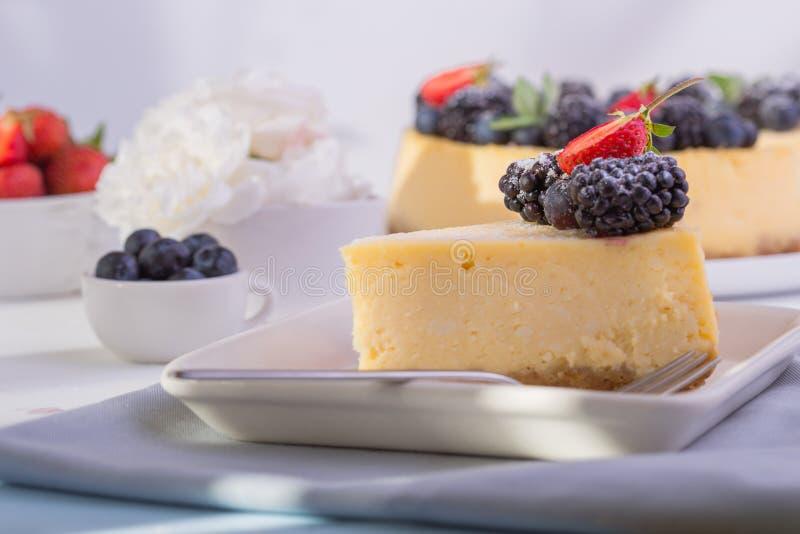 El pastel de queso de Nueva York en la placa blanca adornó la fresa Pastel de queso cocido húmedo y liso delicioso del arándano imagenes de archivo