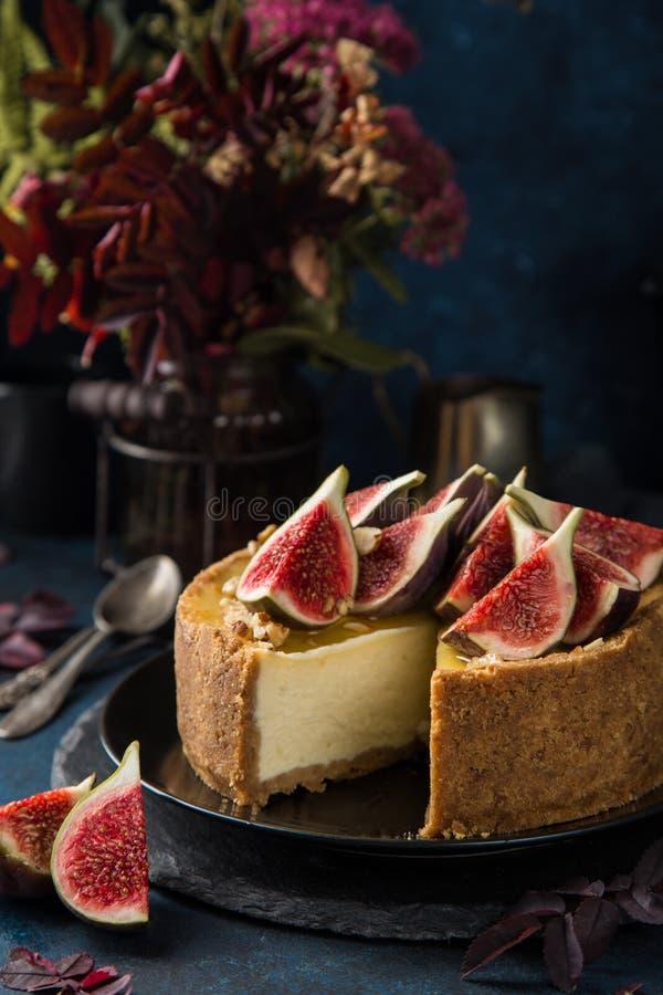 El pastel de queso sirvió con los higos, las nueces y la miel frescos imagen de archivo