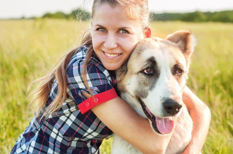 El pastor asiático central de la muchacha y del perro abraza en un parque El caminar con imagen de archivo