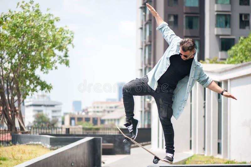 El patinador del muchacho está haciendo truco en la calle imagen de archivo