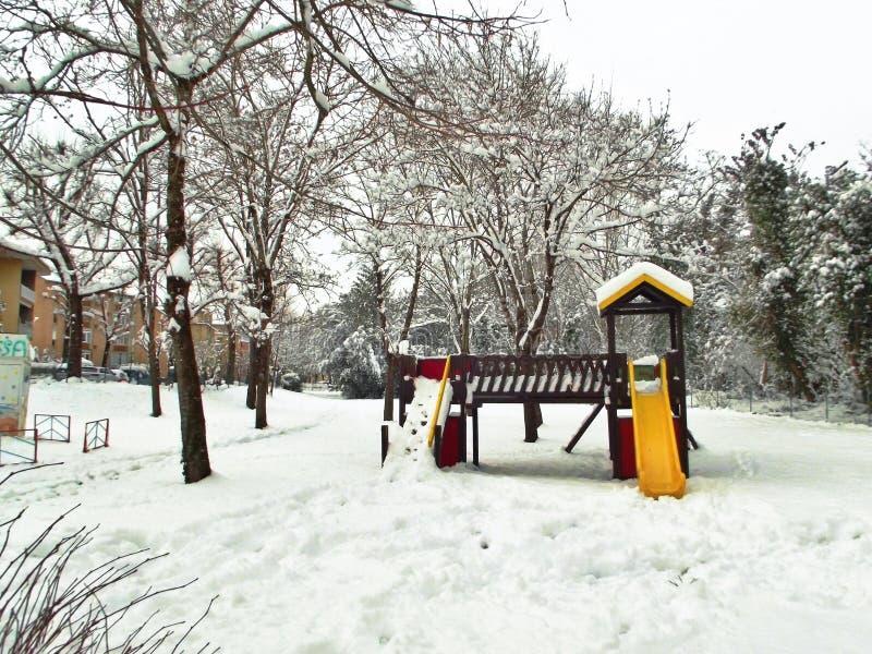 El patio de los niños con la diapositiva amarilla y roja cubierta en nieve imagenes de archivo