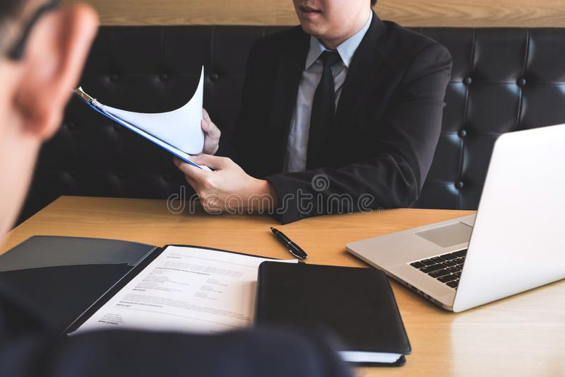 El patrón que llega para una entrevista de trabajo, hombre de negocios escucha las respuestas del candidato que explica sobre su  fotografía de archivo libre de regalías