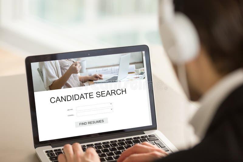 El patrón que usa el ordenador portátil que busca a los candidatos, hallazgo reanuda en línea fotografía de archivo