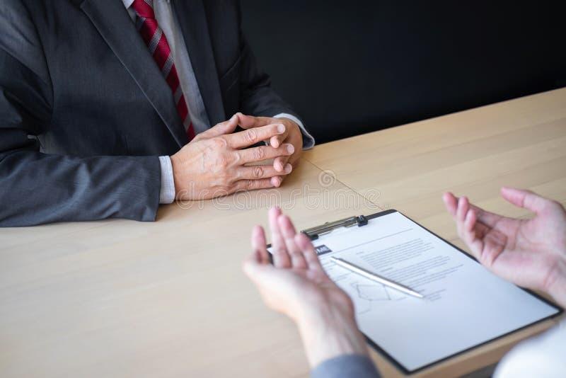 El patr?n que llega para una entrevista de trabajo, hombre de negocios escucha las respuestas del candidato que explica sobre su  imagen de archivo libre de regalías