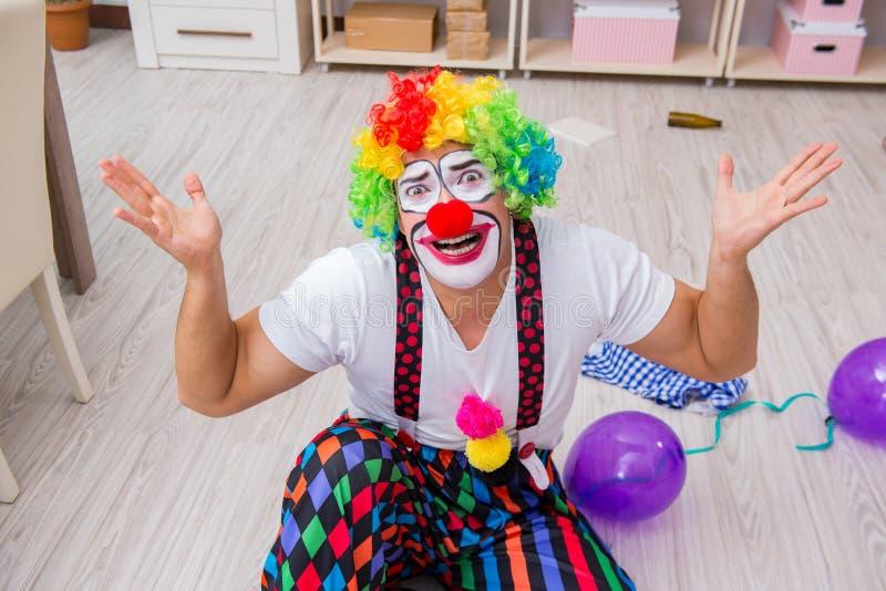 El payaso borracho que celebra teniendo un partido en casa foto de archivo
