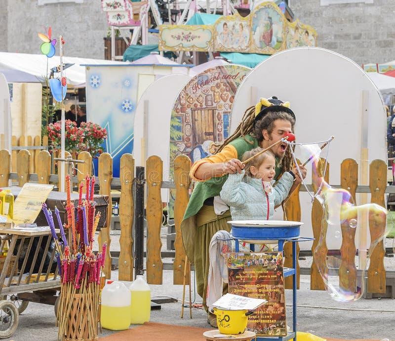 El payaso infla burbujas de jabón Oktoberfest en Salzburg foto de archivo