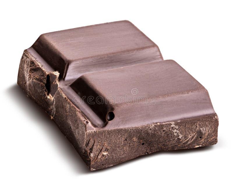 El pedazo de chocolate negro se aísla en un fondo blanco imágenes de archivo libres de regalías